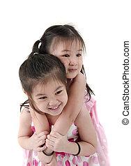 Two little girls sharing an apple