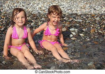 two little girls sit ashore in water