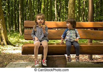 two little girls sit on the bench