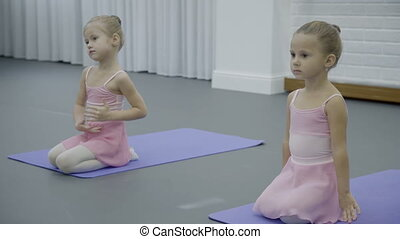 Two little girls sit on their laps and do dance exercises on...