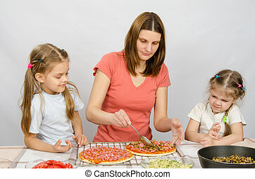 Two little girls sitting at the kitchen table and watch as a mother preparing a pizza