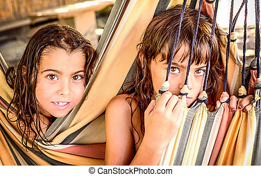 Two little girls sitting in the hammock on the beach
