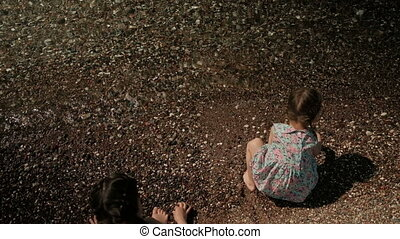 Two little girls sitting on shore of lake with backs...
