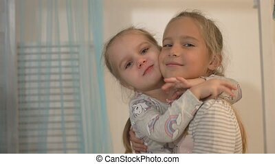 Two little girls smile and hug at home - Two beautiful...