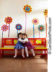 Two little girls smile and hug at school - Caucasian and...