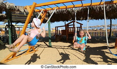 two little girls swinging on a swing at the beach