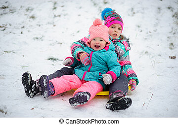 Two little girls together move down from a hill on the...