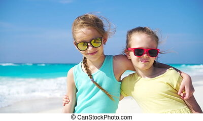 Two little girls together on the beach on caribbean vacation. Portrait of two kids outdoors