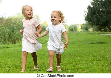 Two little girls walking in the park