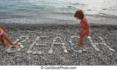 two little girls walking on BEACH inscription from stones in pebble beach