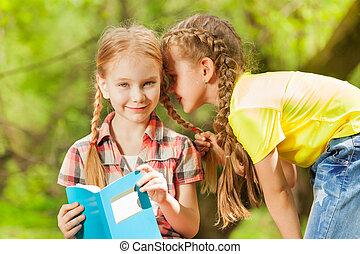 Two little girls whispering secrets in the ear