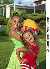 Two little girls with a ball