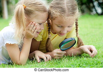 Two little girls with magnifying glass outdoors in the day time