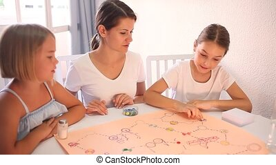 Woman with two kids playing board games together sitting at table in living room