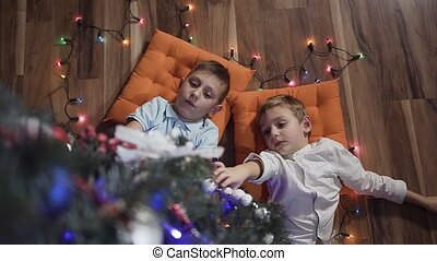 Two little guys have fun lie on orange pillows near a...