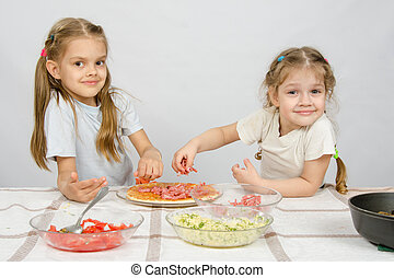 Two little happy girl at the table spread on the pizza ingredients