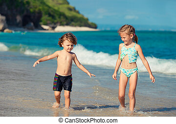 two little kids playing at the beach in the day time