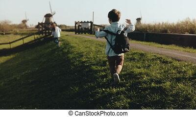 Two little kids playing near old windmill farm. Happy...
