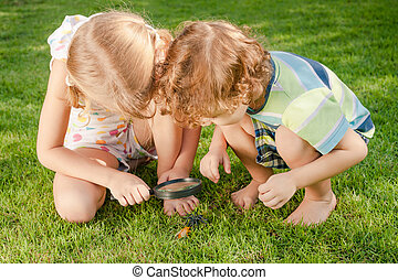 Two little kids playing with magnifying glass outdoors in the day time