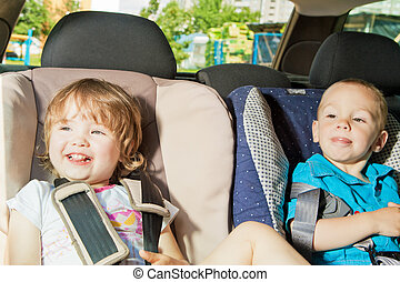 two little kids sitting on back seat in child safety seats...