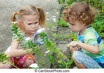 Two little kids with magnifying glass outdoors in the day time