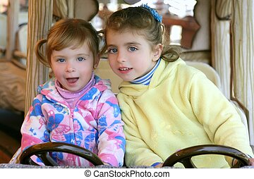 Two little sister girls driving car on fairground
