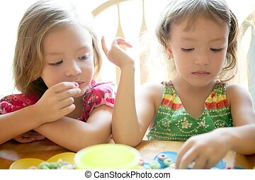 Two little sister girls eating together