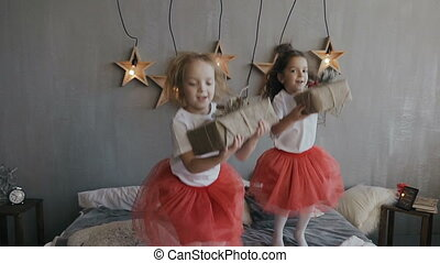 Two little sisters have fun jumping on the bed and holding Christmas gifts in their hands. On a gray wall hangs 6 decorative wooden stars that shine with lights