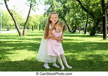 Two little sisters in the summer park