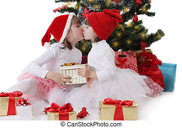 Two little sisters kissing under Christmas tree