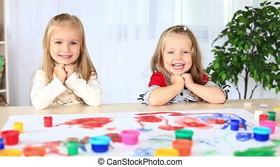 Two little sisters laugh.