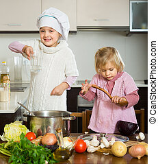 Two happy little sisters learning how to cook at domestic kitchen.