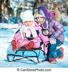 two little sisters on a sled