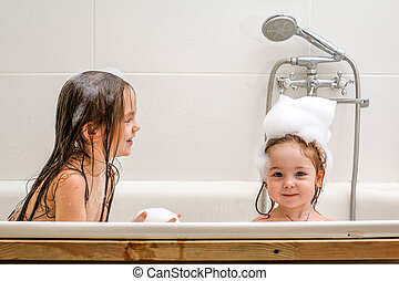 Two little sisters play in a bath.