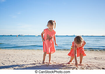 Two little sisters playing together on the white beach