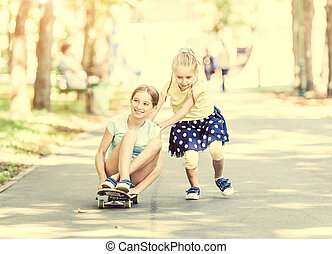 two little sisters playing with a skateboard