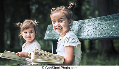 Two little sisters reading a book