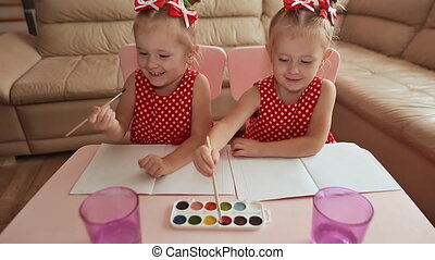 Two little sisters twins are happy to paint drawings with watercolors sitting at the table together.