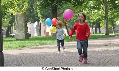 two little sisters with balloons running in the park, Slow motion