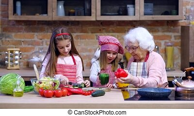 Two little sisters with granny cooking together - Two little...
