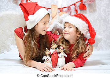 Two little sisters with toy angels
