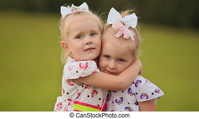 Two little twin sisters are pressed against each other, having fun on a green meadow in summer. Hugging fall on the grass.