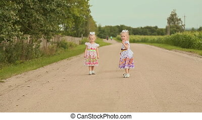 Two little twins sisters in white dresses on the road along the field. Running together. Far Forest.