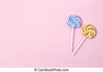 Two lolipop on pink background.