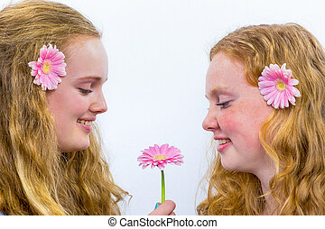 Two long haired girls with pink flowers