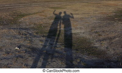Two long shadows of young people on a land in summer in slo-mo