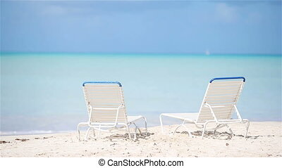 Two lounge chairs on beautiful tropical beach at Maldives -...