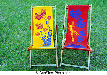 Two lounge chairs on green grass. concept photo copyspace