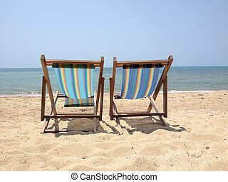 Two lounge chairs on the beach - Two lounge chairs on a...