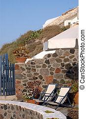 two lounge chairs on stone patio famous oia santorini greek...